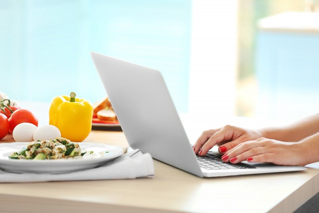peron using a laptop near a plate of healthy food
