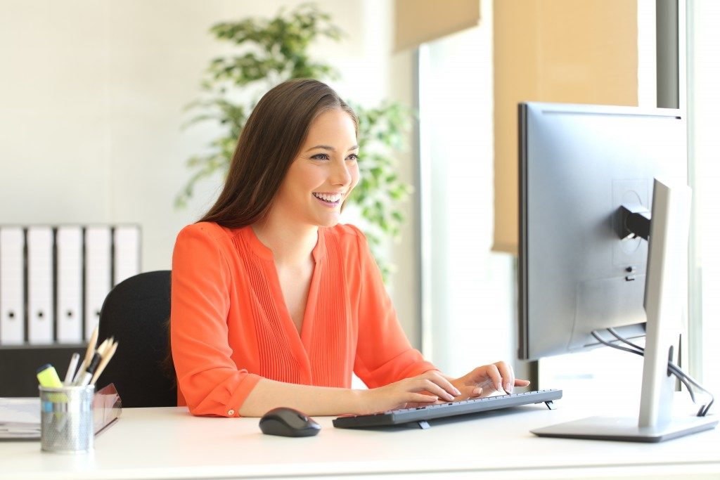 smiling woman working on a desktop