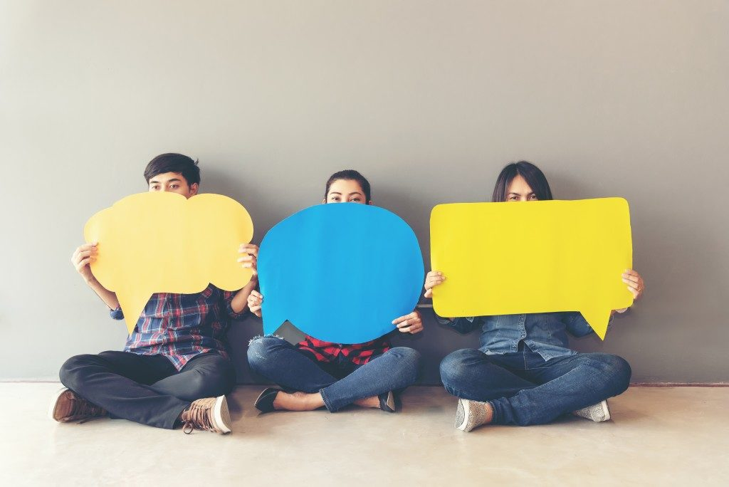 paper cutouts of speech bubbles being held