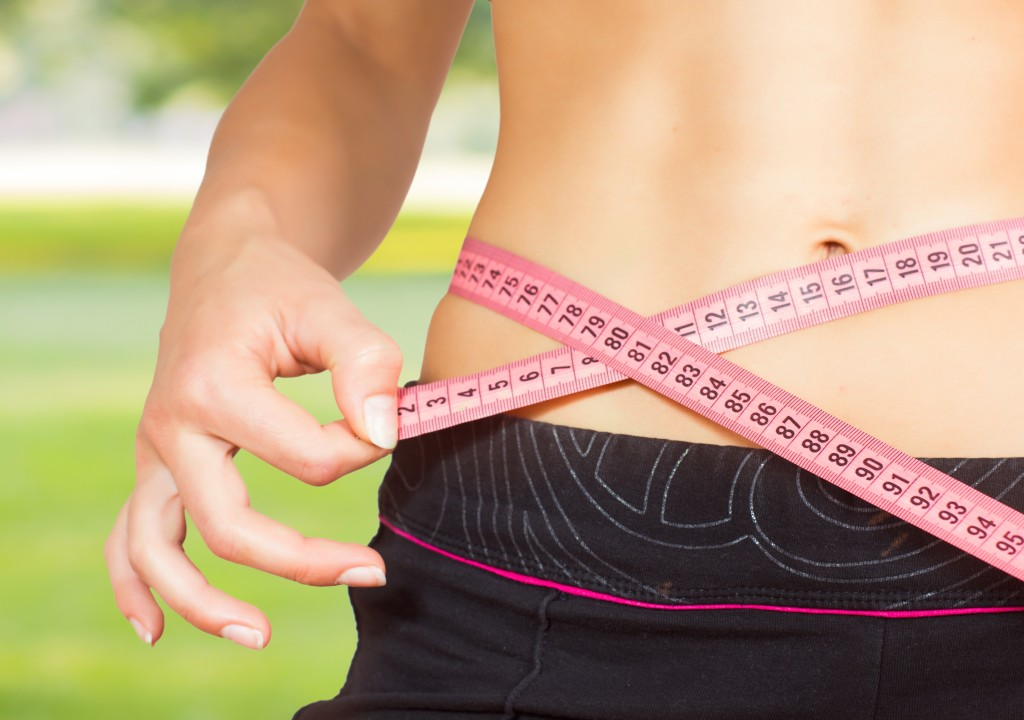Slim Female with perfect healthy fitness body, measuring her thin waist with a tape measure