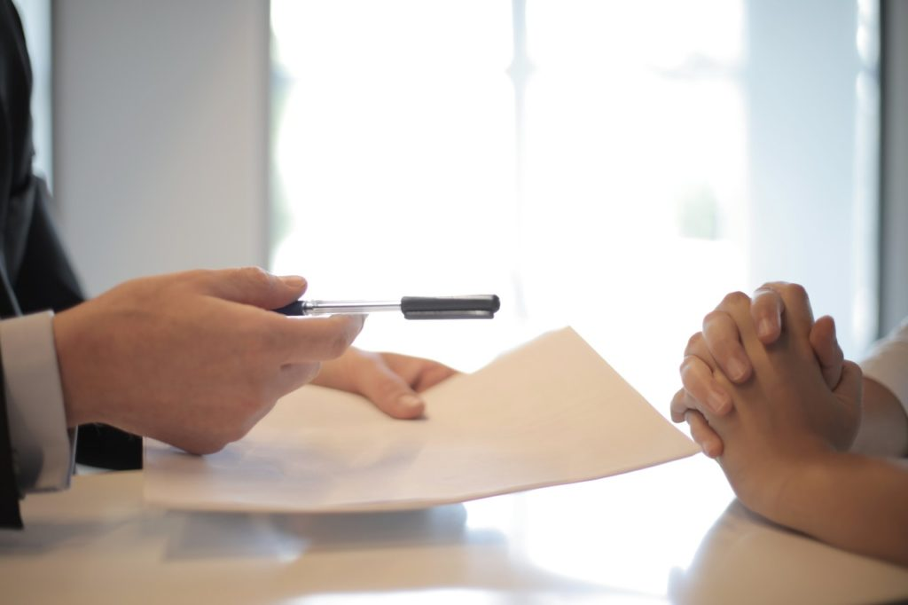 person handing over pen and paper to another person